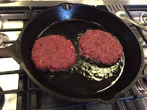 Venison burgers sizzling in the pan.