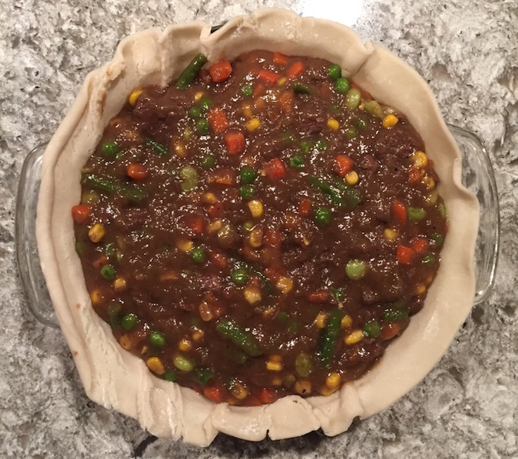 Venison pot pie loaded with filling and ready to be top crusted.
